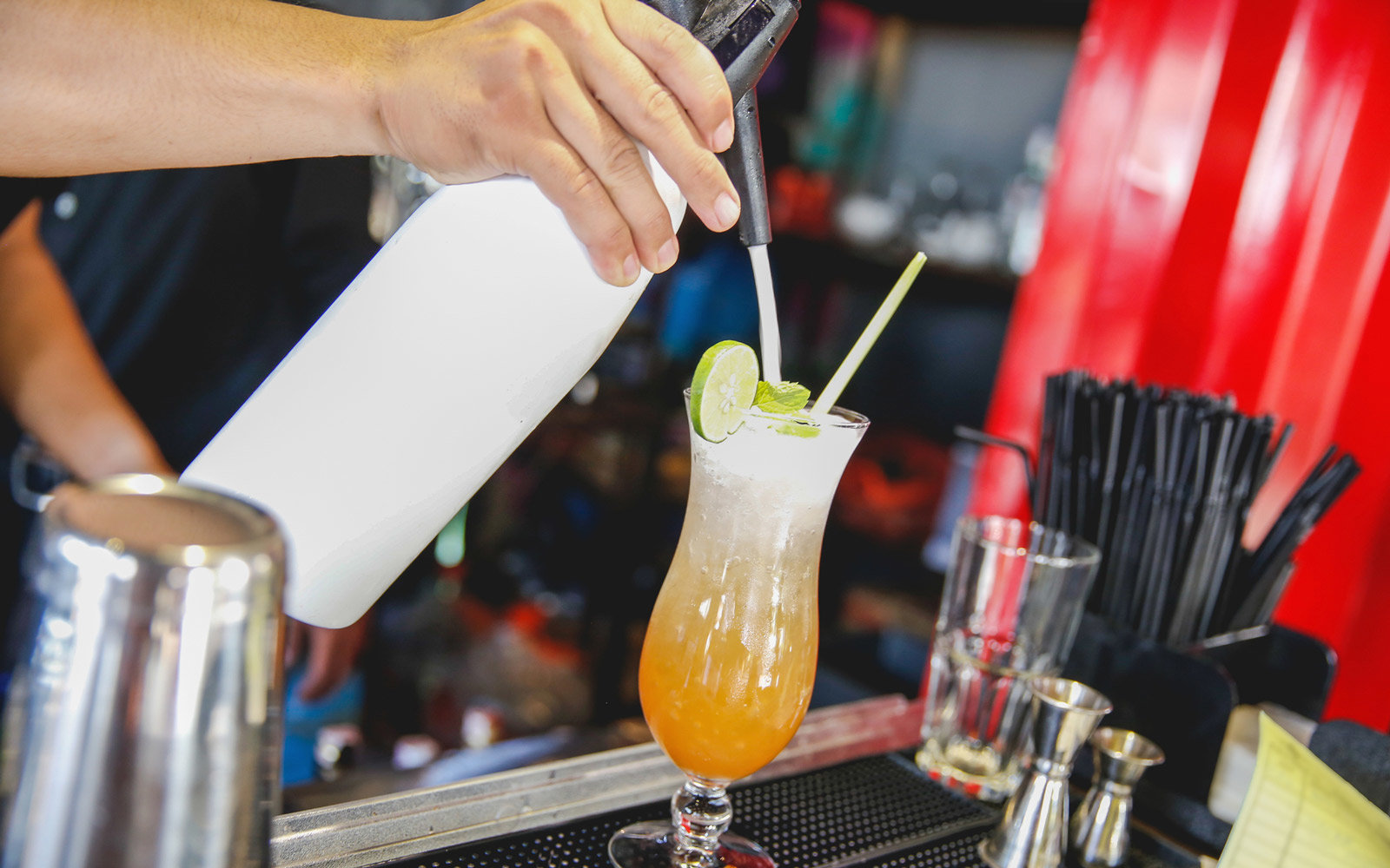 Males bartender pouring white foam on top iced tea