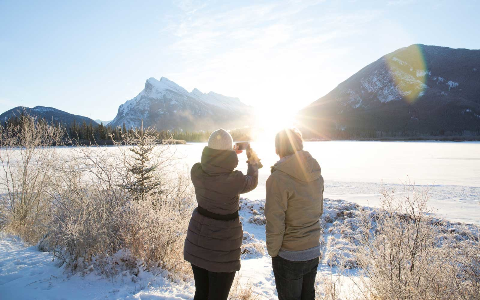 People taking a photo of a frozen lake in the winter