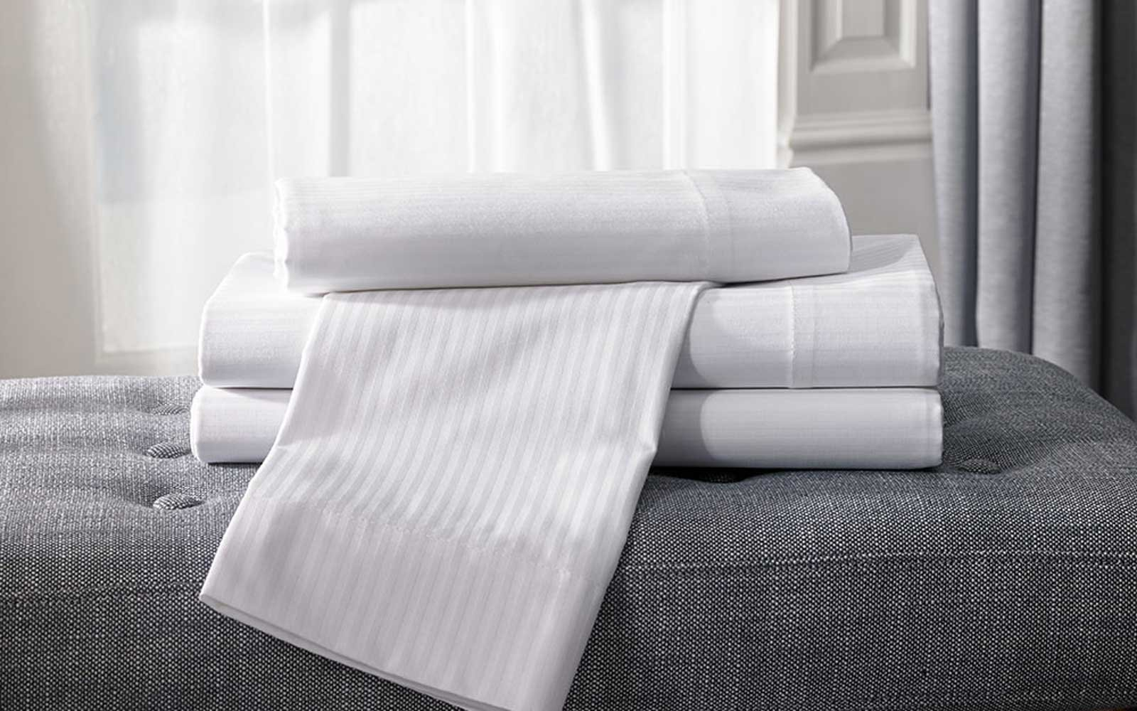 Hilton Hotel Stripe Sheet Set and Feather and Down Pillow & The Best Hotel Bedding and Pillows to Use at Home | Travel + Leisure