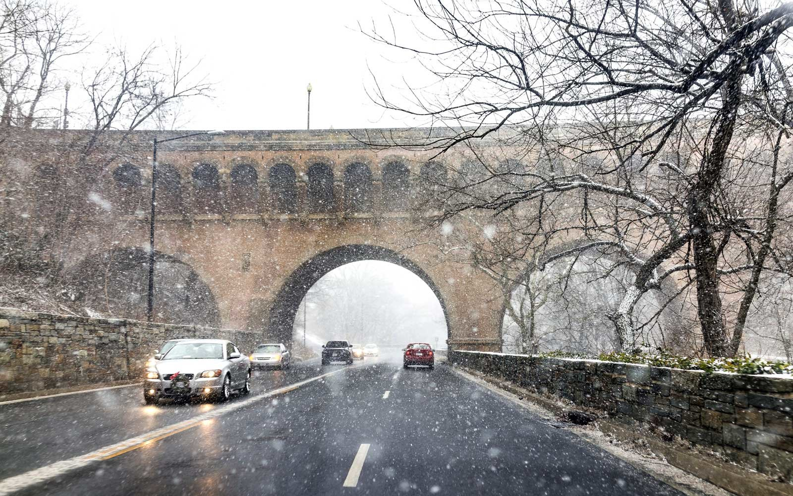 Snow storm with cars and Dumbarton bridge with arches