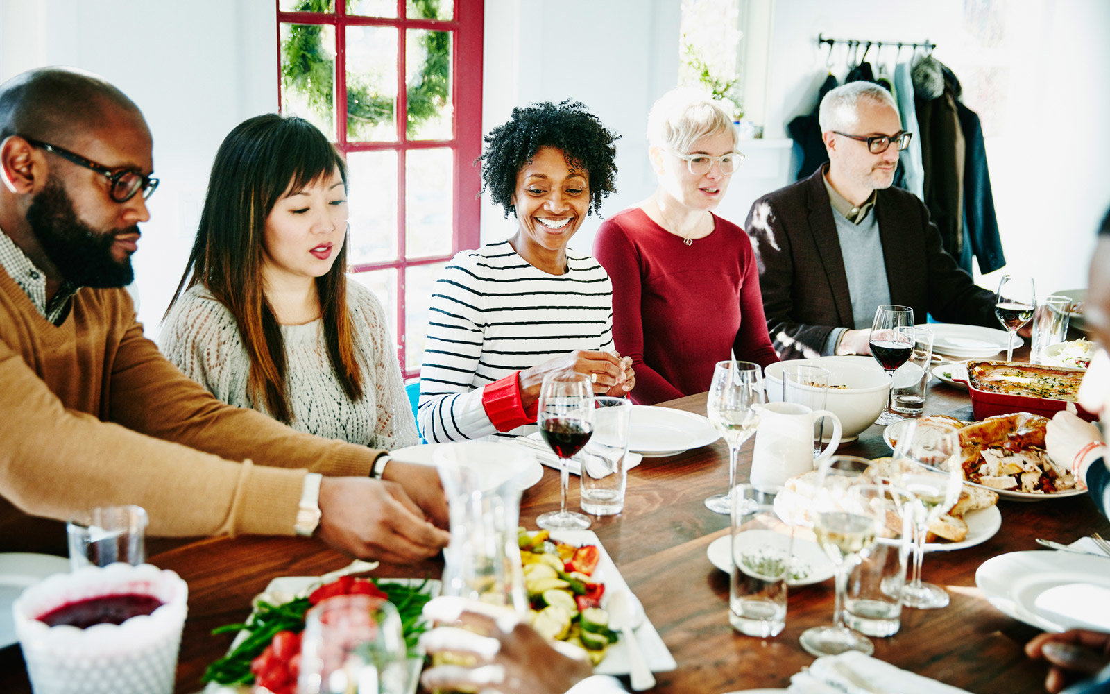 Smiling friends serving each other during holiday meal together