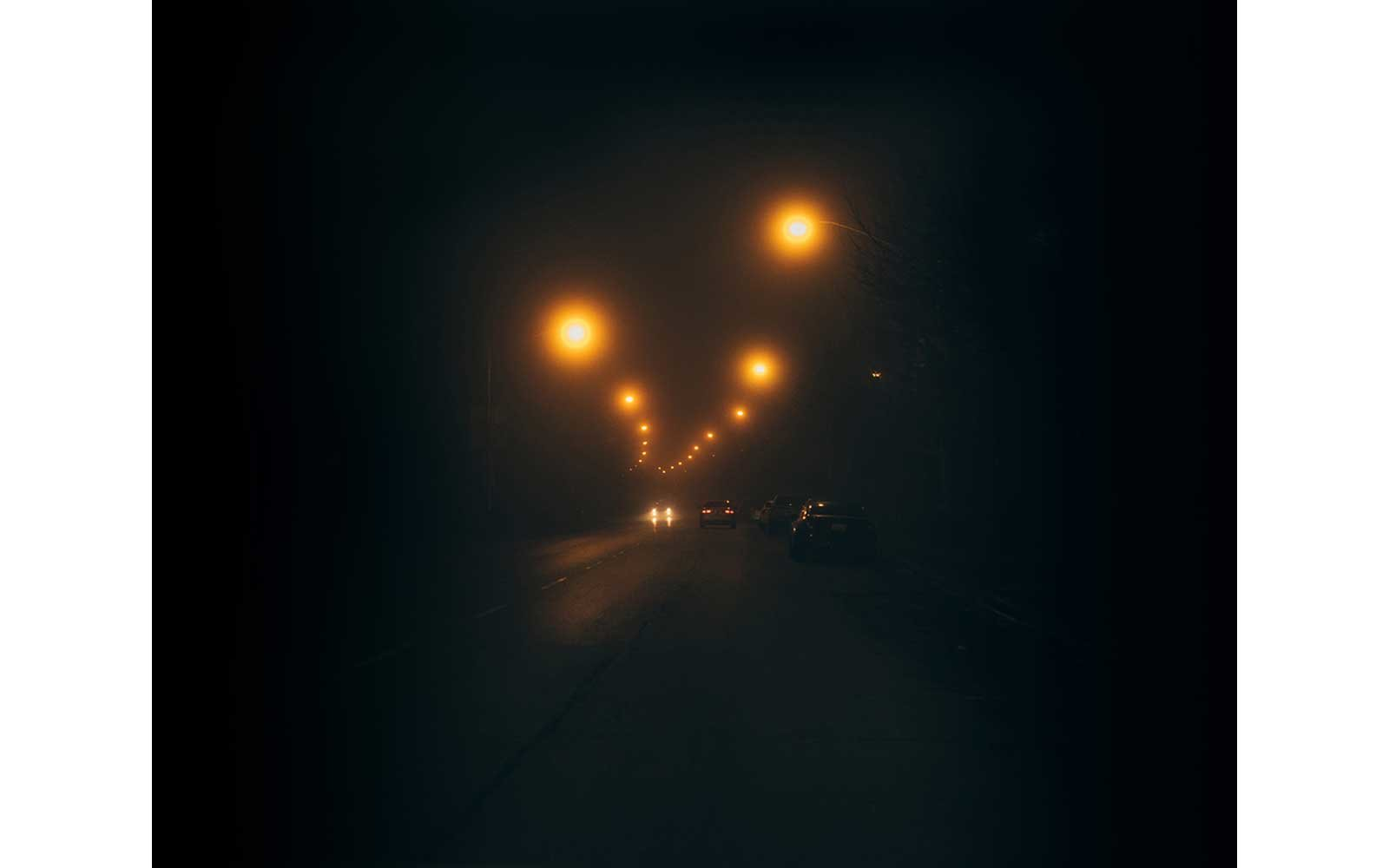 Lights shine through the fog on a road at night