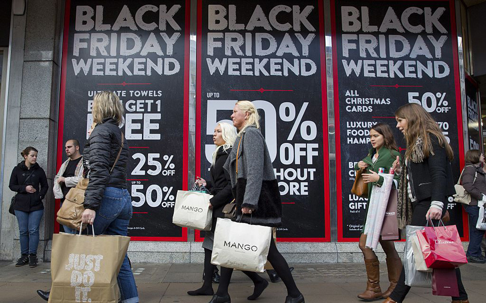Shoppers are pictured walking past 'Black Friday' advertising in shop windows on Oxford Street in central London