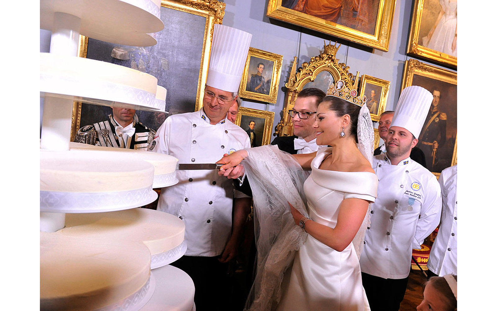 Crown Princess Victoria of Sweden and Prince Daniel, Duke of Vastergotland cut their wedding cake during the Wedding Banquet at the Royal Palace