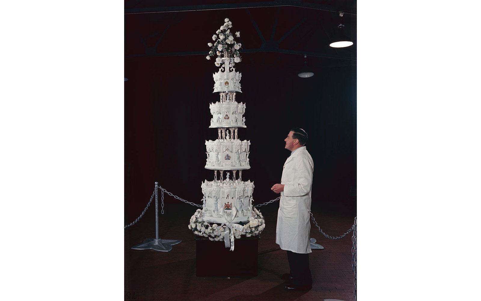 A man standing by the nine-foot high wedding cake made at Huntley and Palmers Factory in Reading, Berkshire, for the wedding of Princess Elizabeth (later Queen Elizabeth II) to Phillip Mountbatten