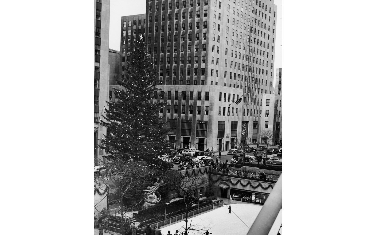Arial view of the ice rink and decorated Christmas tree in Rockefeller Plaza, New York, New York, circa 1950s