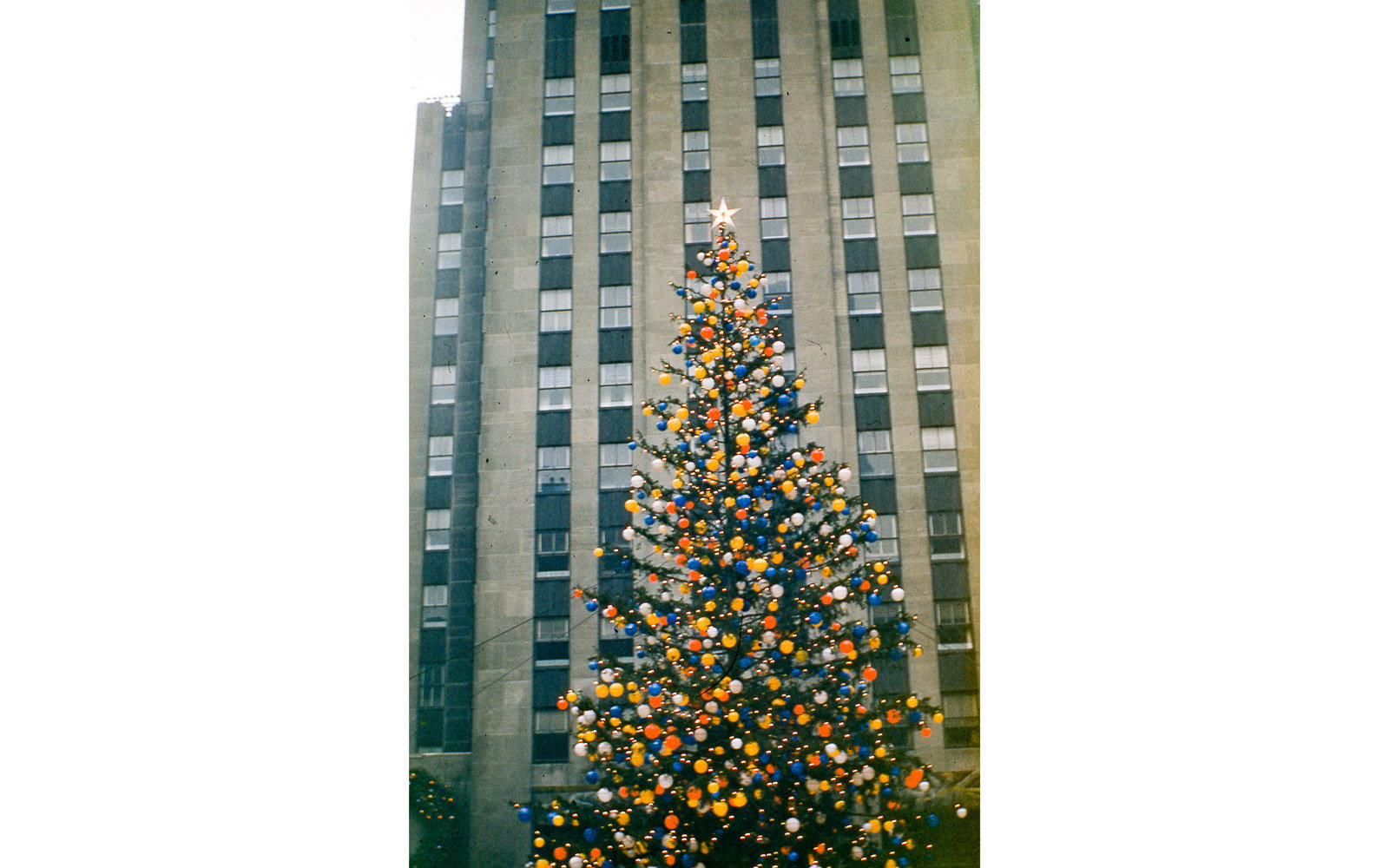 View of the Rockefeller Center Christmas tree fully adorned in colored globe lights and a 5-pointed star, in Rockefeller Center Plaza, midtown Manhattan, New York City, December, 1955