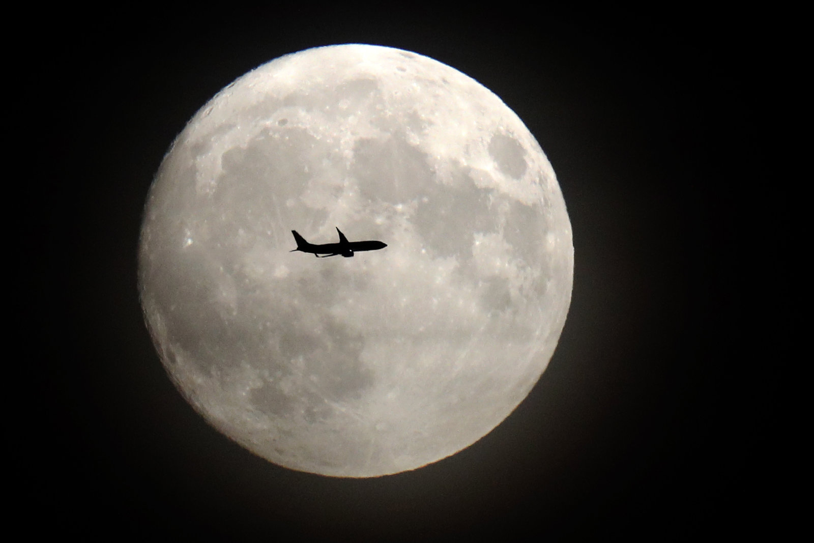 A supermoon with a plane flying in front of