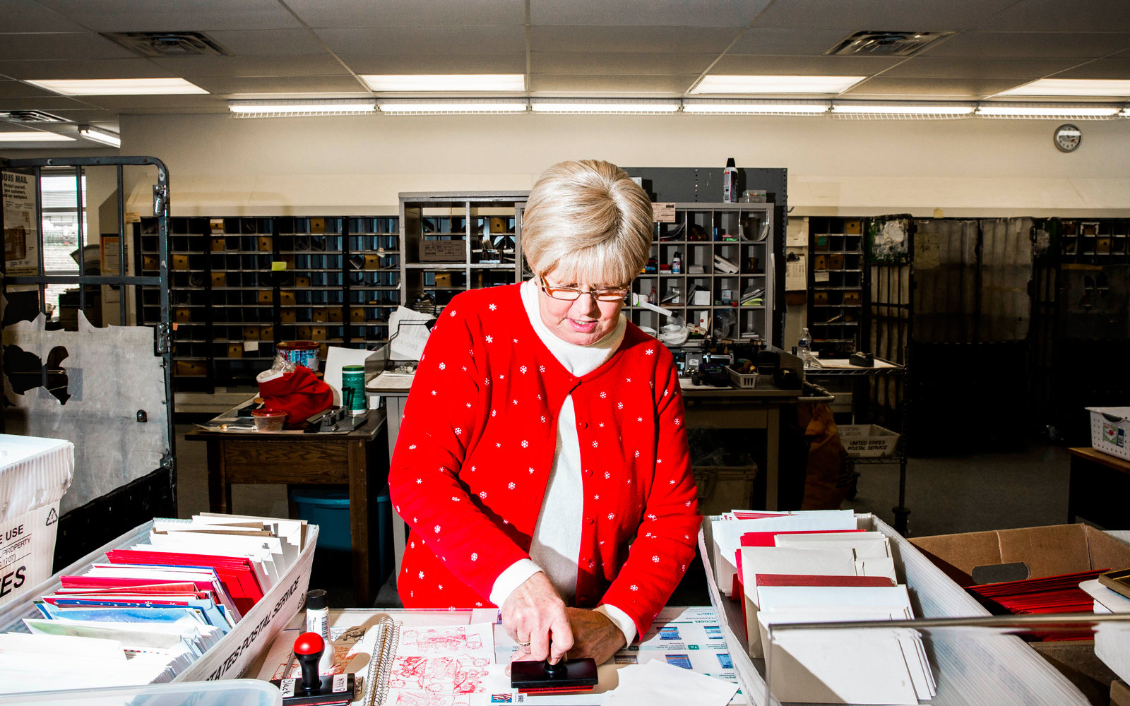 Postal Worker stamps letters to children around the world