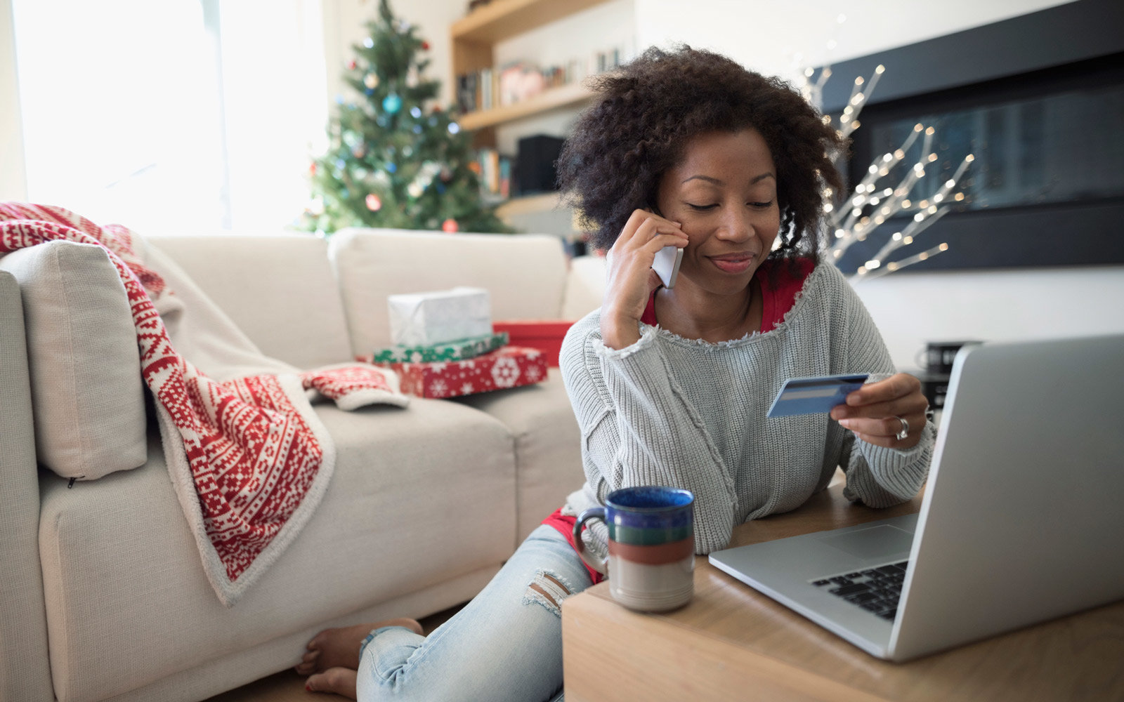 Woman with credit card talking on smart phone, Christmas shopping at laptop in living room