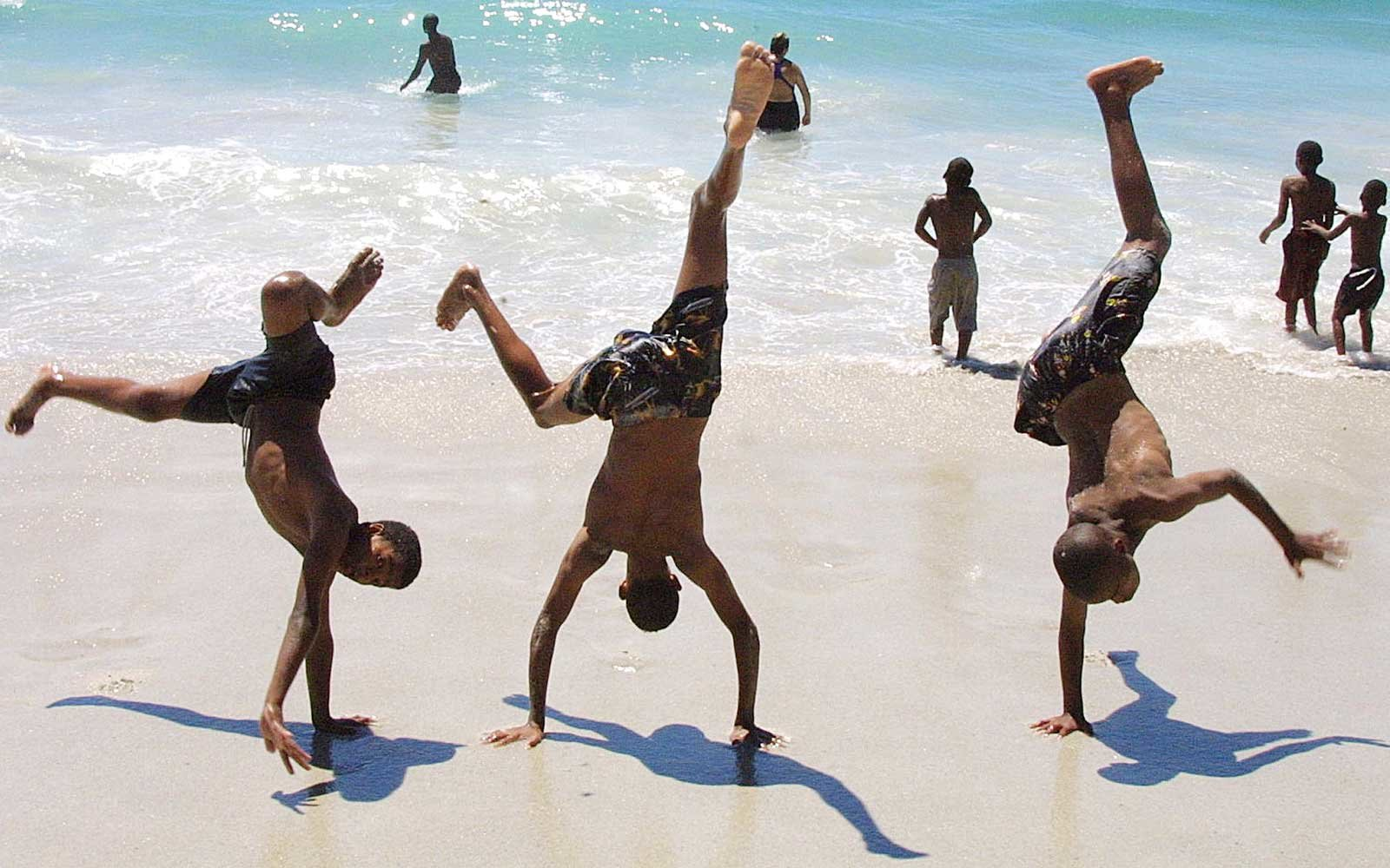Holiday-makers frolic at the water's edge on Camp's Town Beach, South Africa