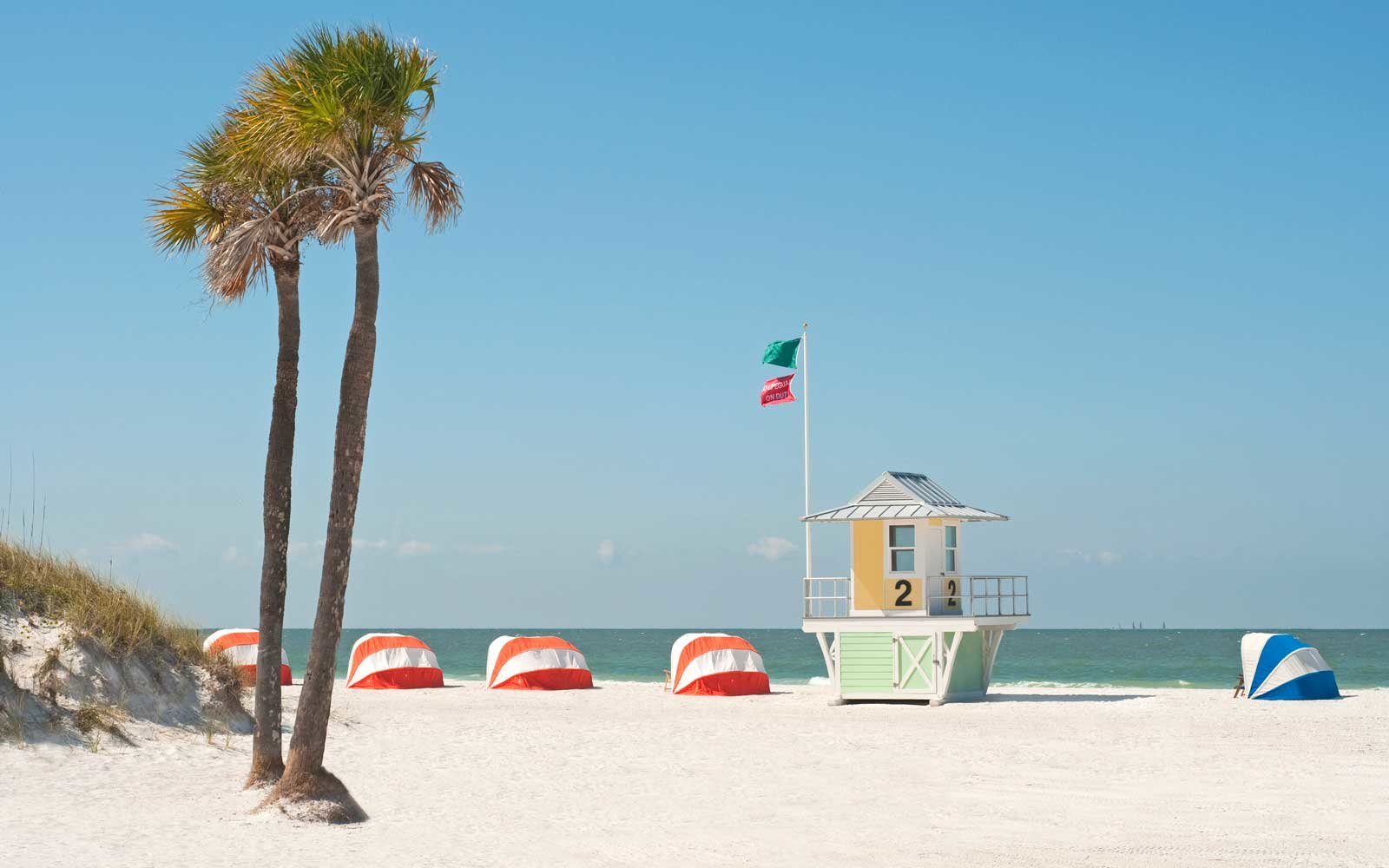 Lifeguard hut on beach with palm trees and beach tents in Clearwater, Florida