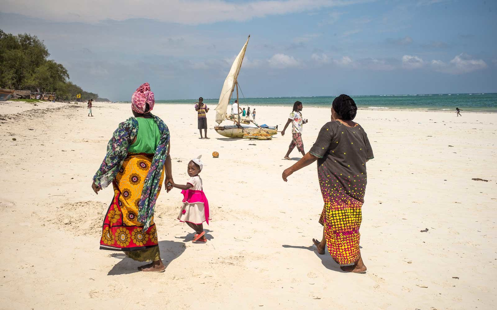 A grandmother and her grandchild walking on Diani Beach, Kenya