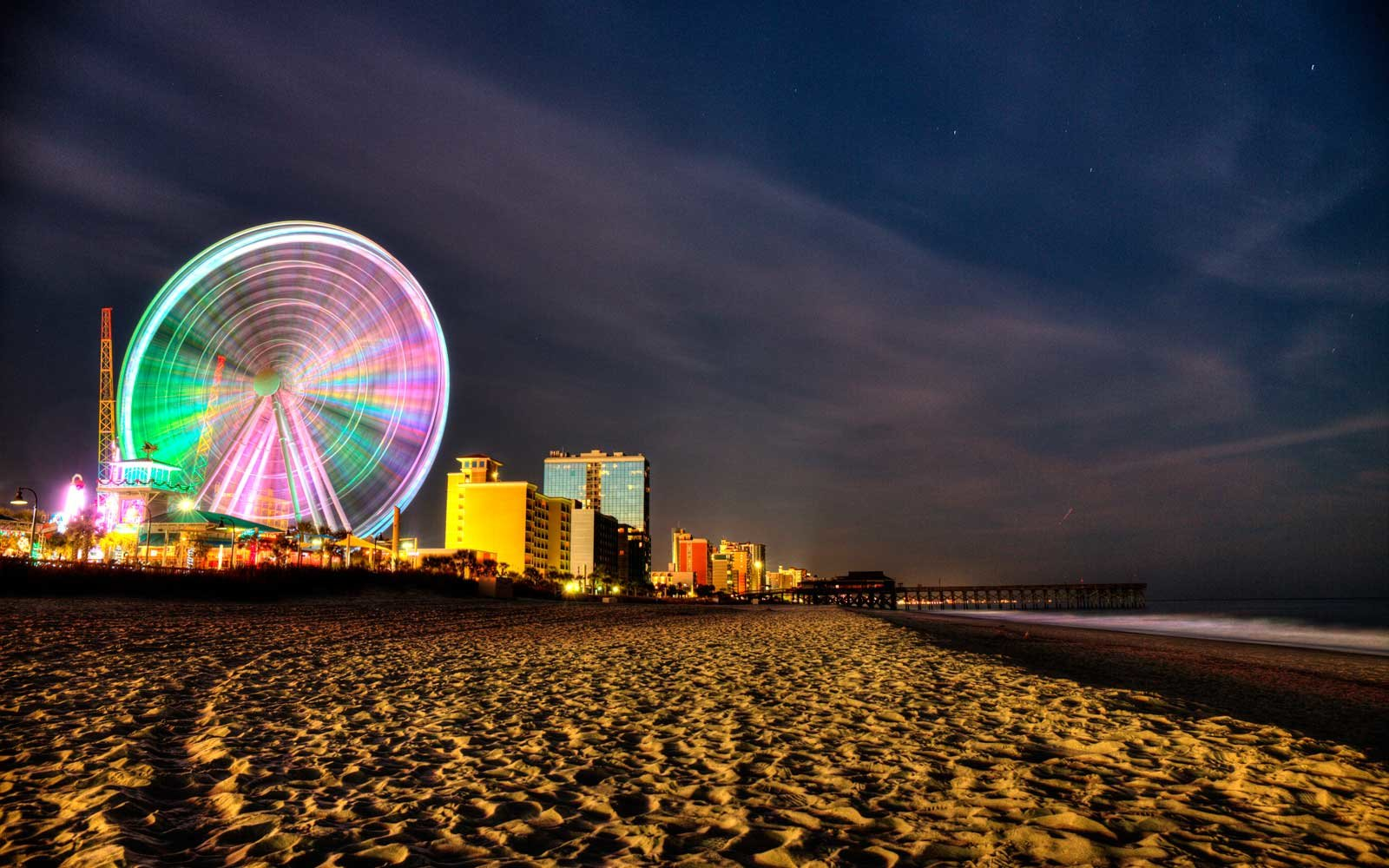 Myrtle Beach boardwalk and ferris wheel lit up at night.