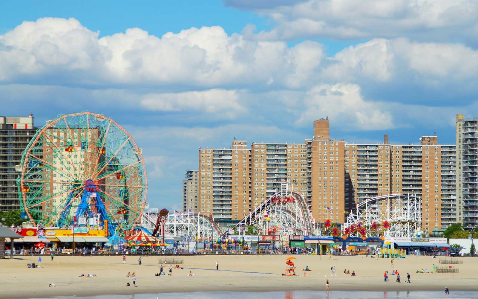 View of Coney Island Beach and Riegelmann Boardwalk in summer day. Photo shows also Wonder Wheel and Cyclone Rollercoaster in the Lunapark.