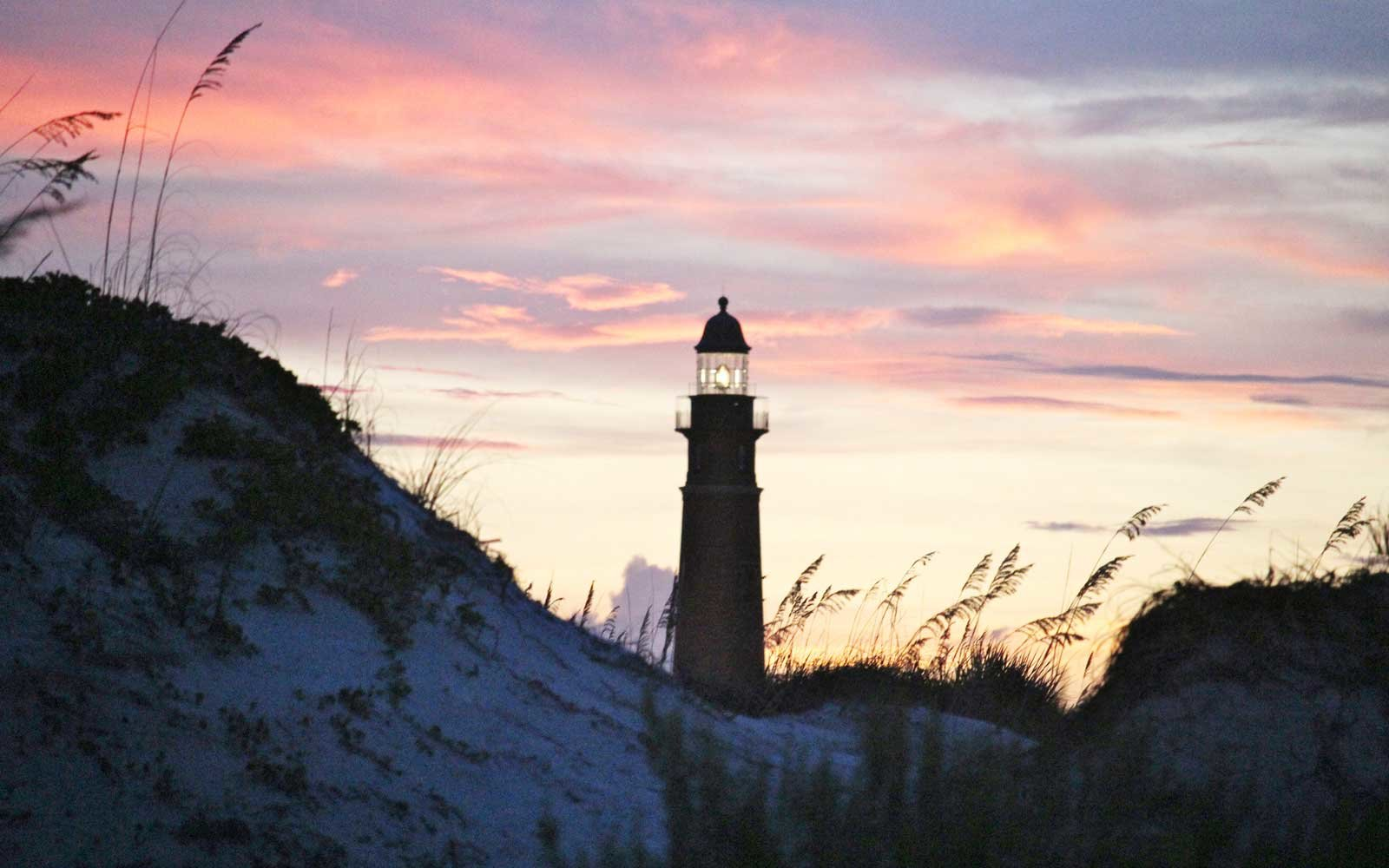 The Ponce de Leon Inlet Lighthouse silhouetted at dusk by brilliant pink and purple clouds swirling at sunset