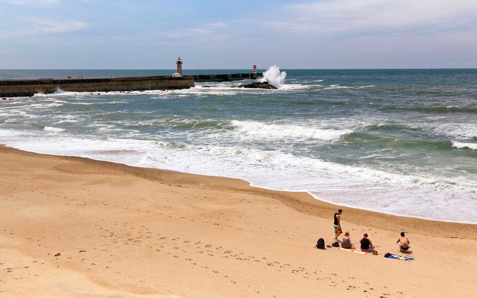 People on the  Praia dos ingleses beach with view of Foz do Douro lighthouse