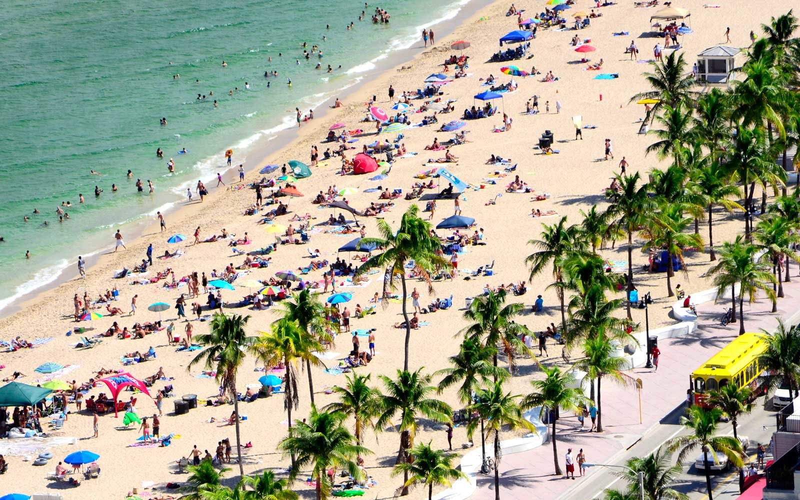 Overhead view of sunbathers lining the beach to soak up the sun and fun at Fort Lauderdale Beach