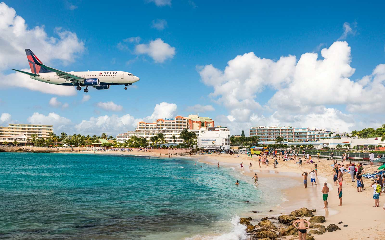 A jet approaches Princess Juliana Airport above onlookers on Maho Beach.