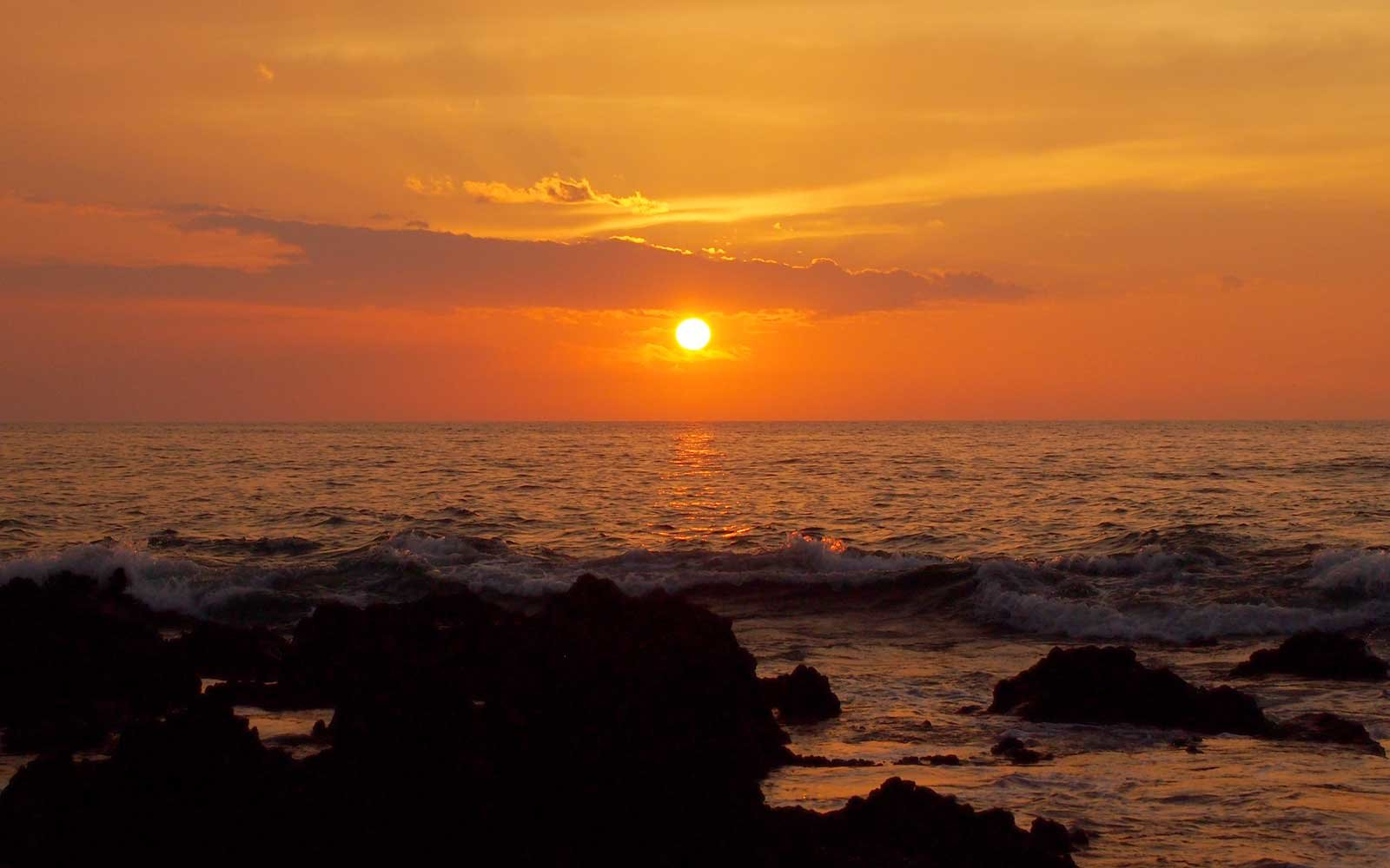 Sunset over ocean with lava rocks of Holoholokai Beach in the foreground