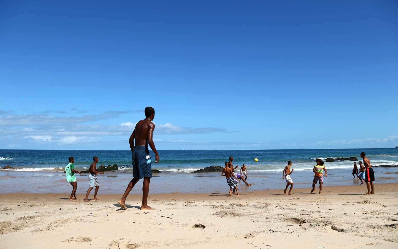 Locals play beach football on a Sunday morning along the Praia do Farol da Barra - Lighthouse beach
