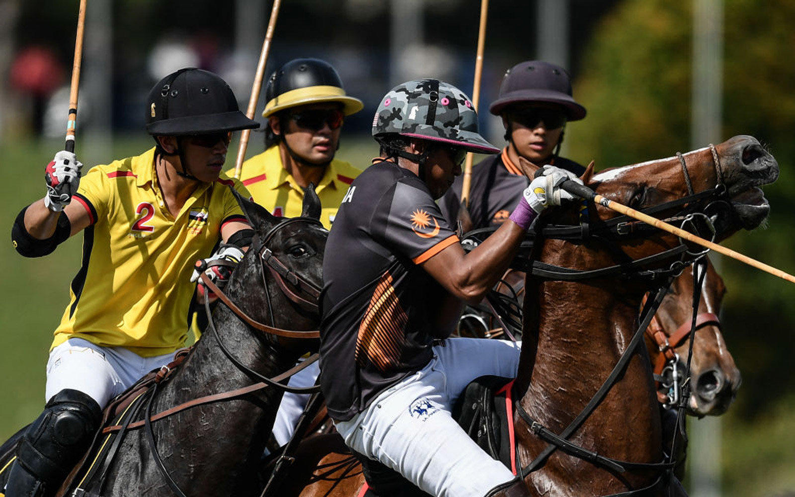This picture taken on August 22, 2017 shows Brunei's Abdul Mateen Bolkiah (L) fighting for the ball against Malaysian players during their equestrian polo match at the 29th Southeast Asian Games (SEA Games) in Putrajaya, outside Kuala Lumpur