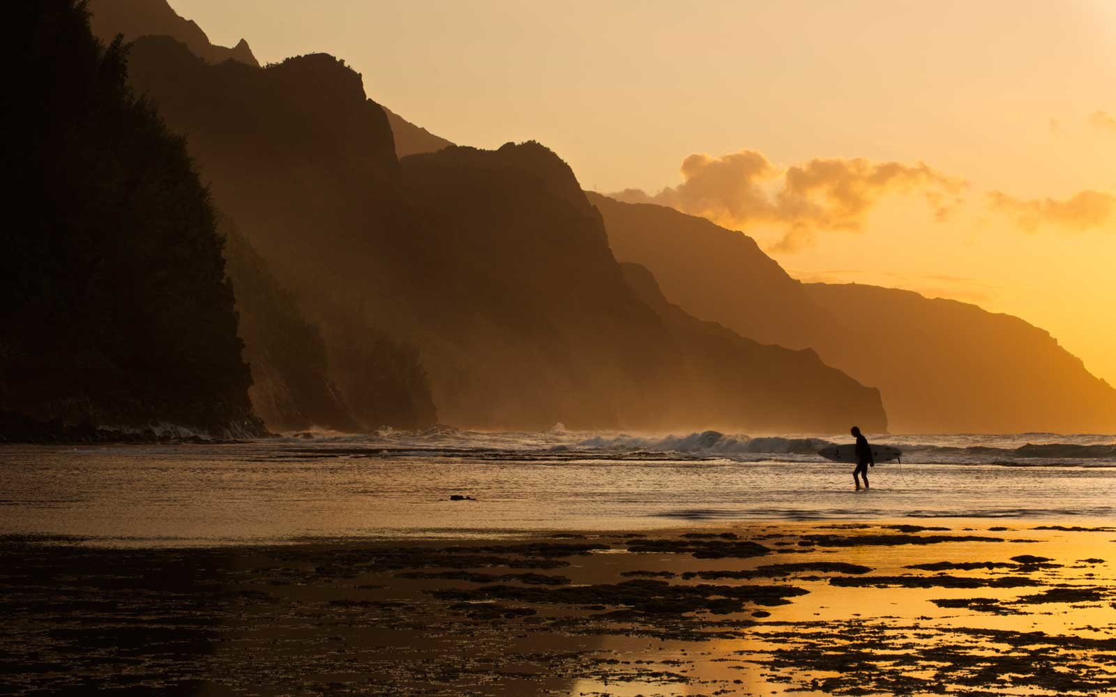 Surfer on beach and Na Pali Coast seen from Ke'e beach, Ha'ena, Kauai, Hawaii
