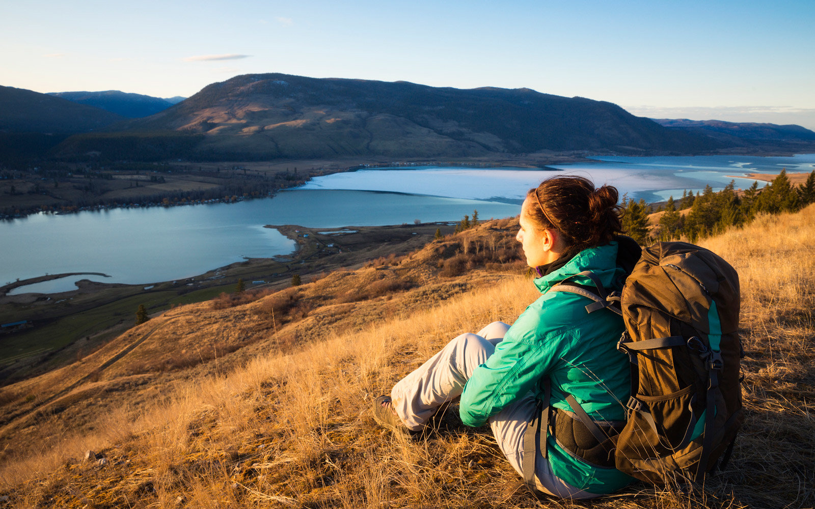 Female hiker enjoying a winter sunset in the Okanagan Valley, British Columbia, Canada