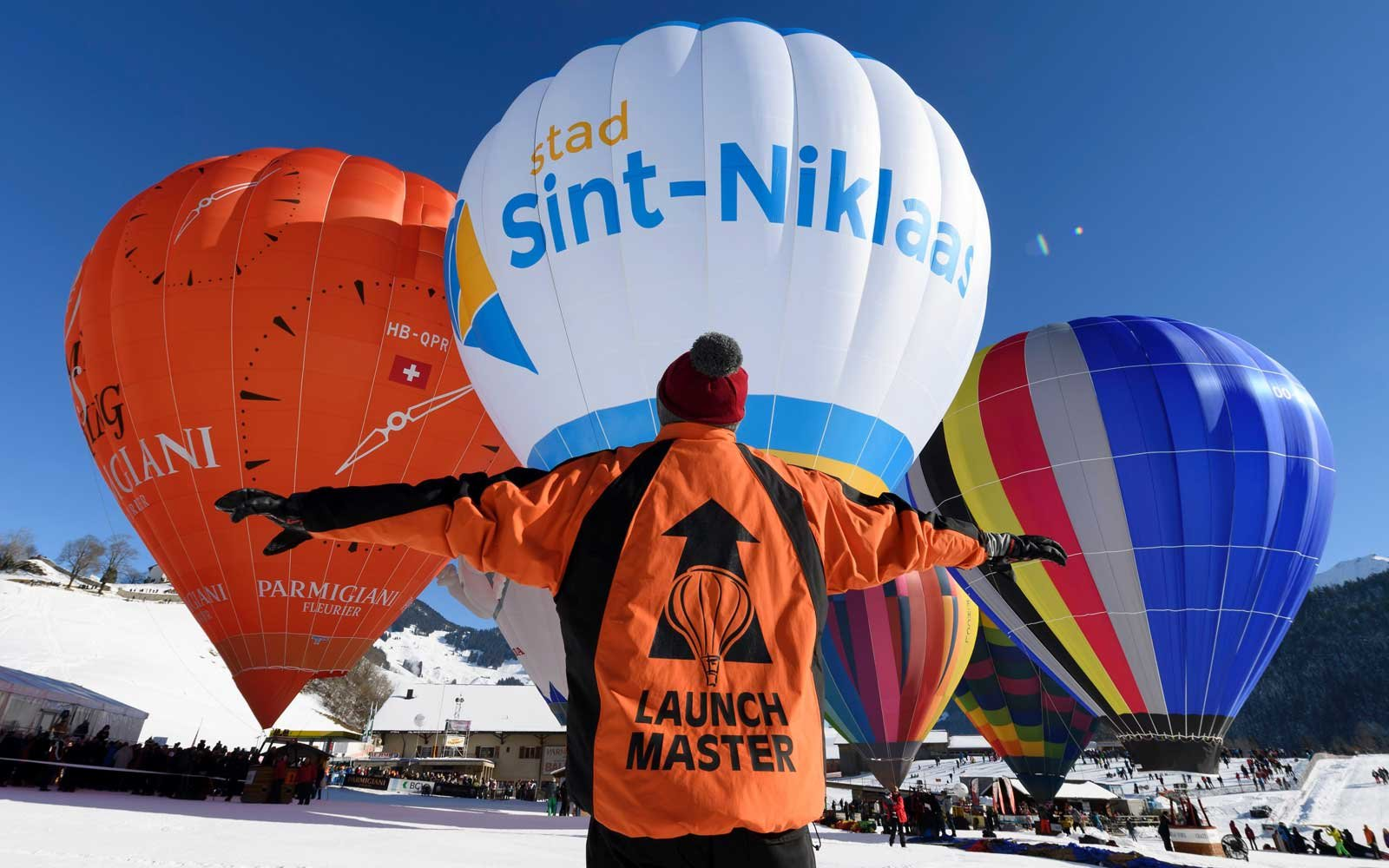 A launch master coordinates hot air balloons on January 21, 2017 at the Chateau-d'Oex ski resort, on the opening day of the 39th International Hot Air Balloon festival