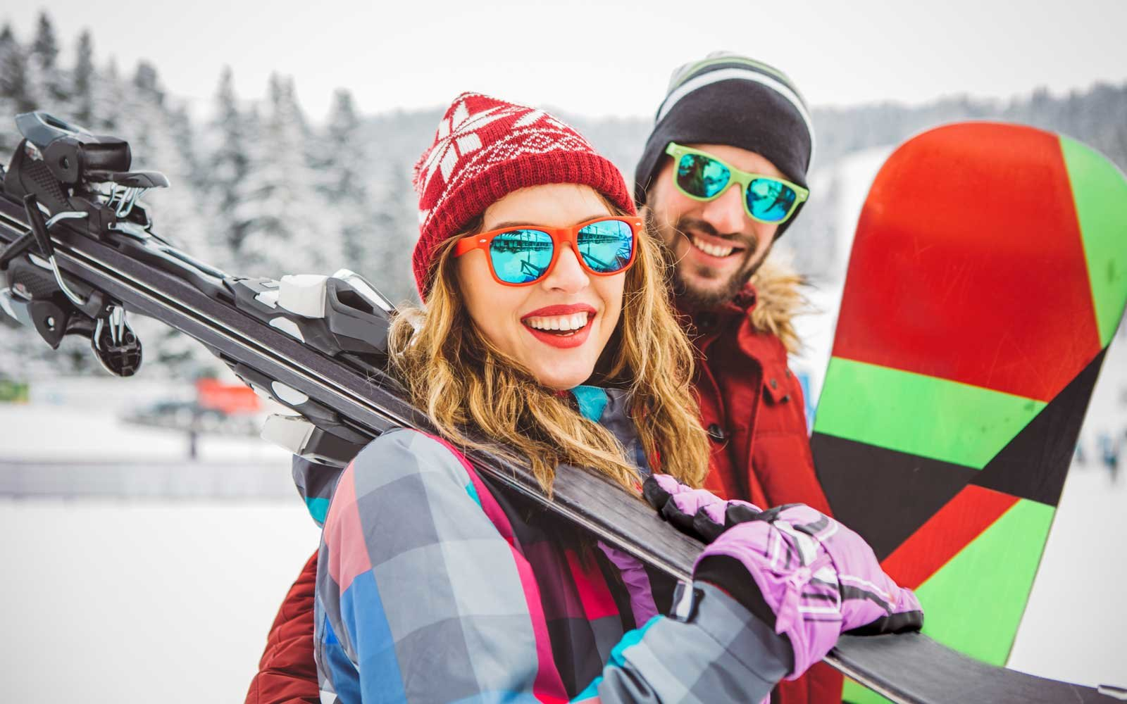 Couple skiing in brightly colored ski gear