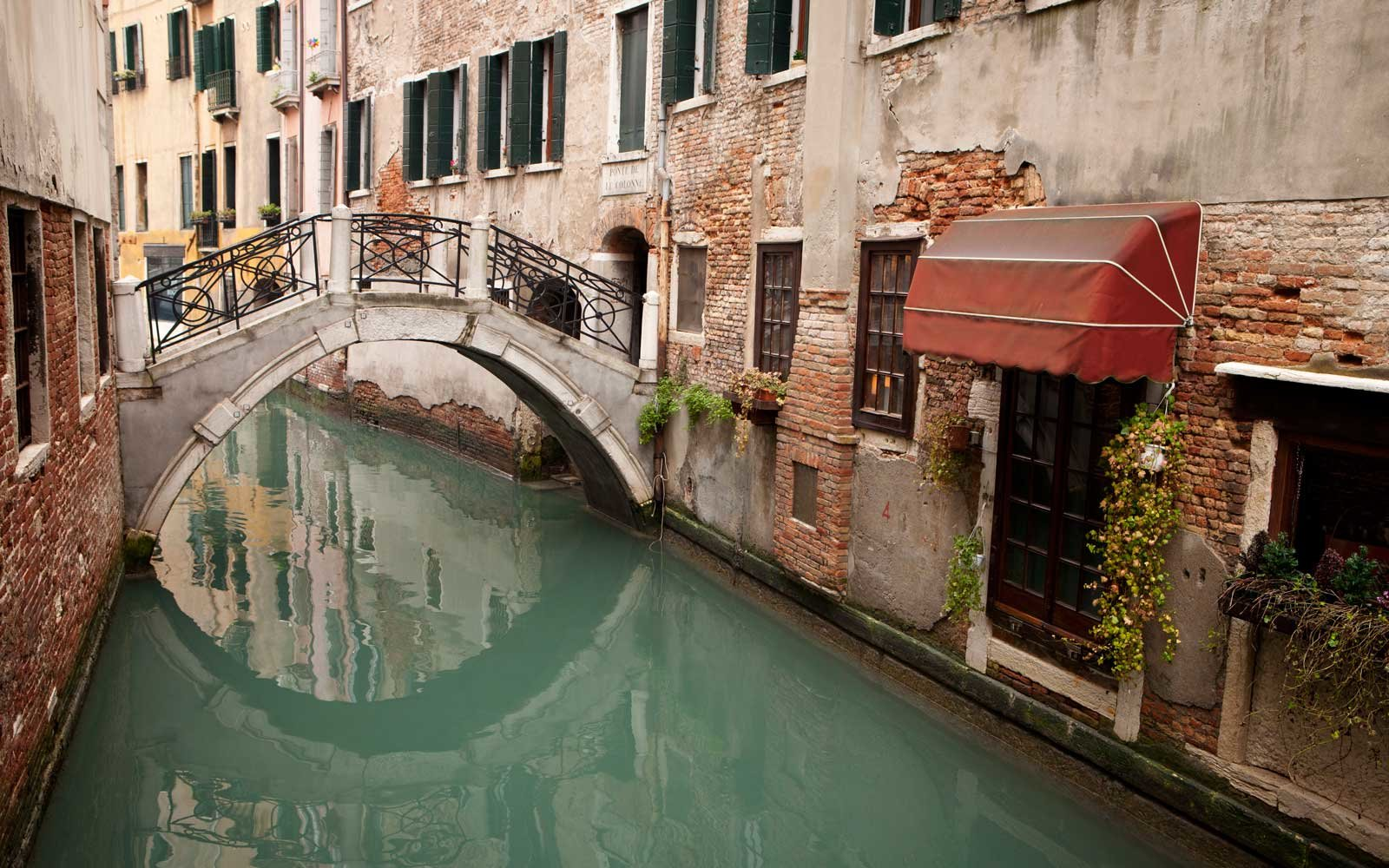 Water canal in Venice with bridge reflection
