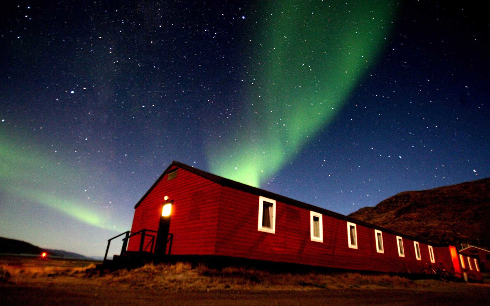The Aurora Borealis glows in the sky in the Greenland town of Kangerlussuaq