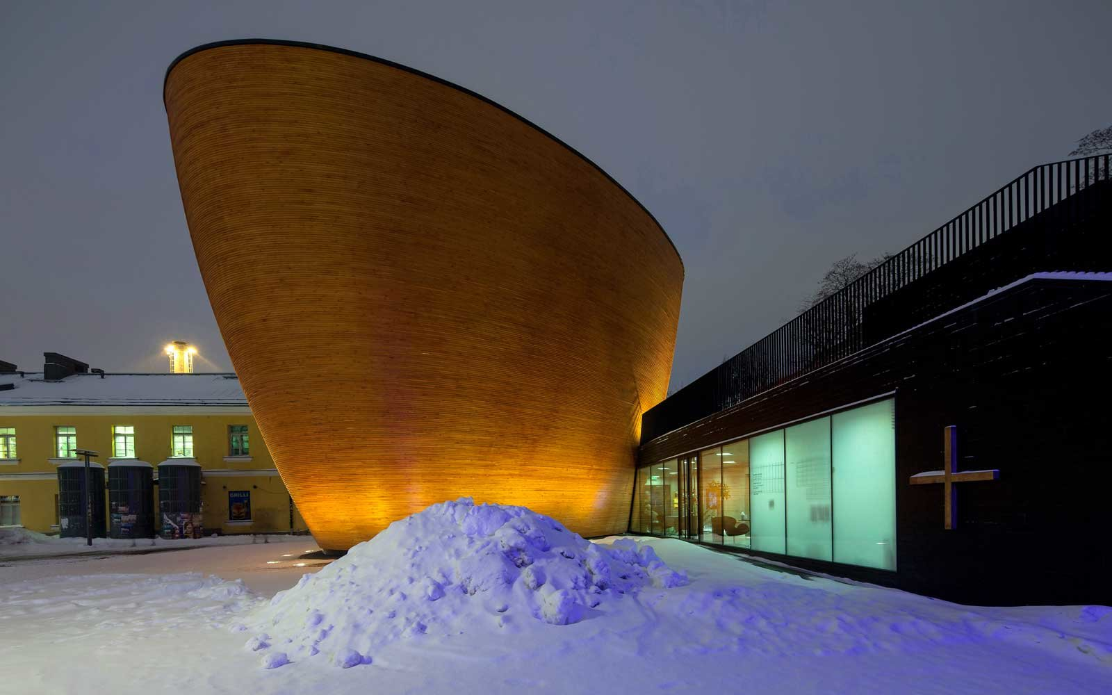 An exterior view of a modern building in Helsinki, Finland called the Kamppi Chapel of Silence.
