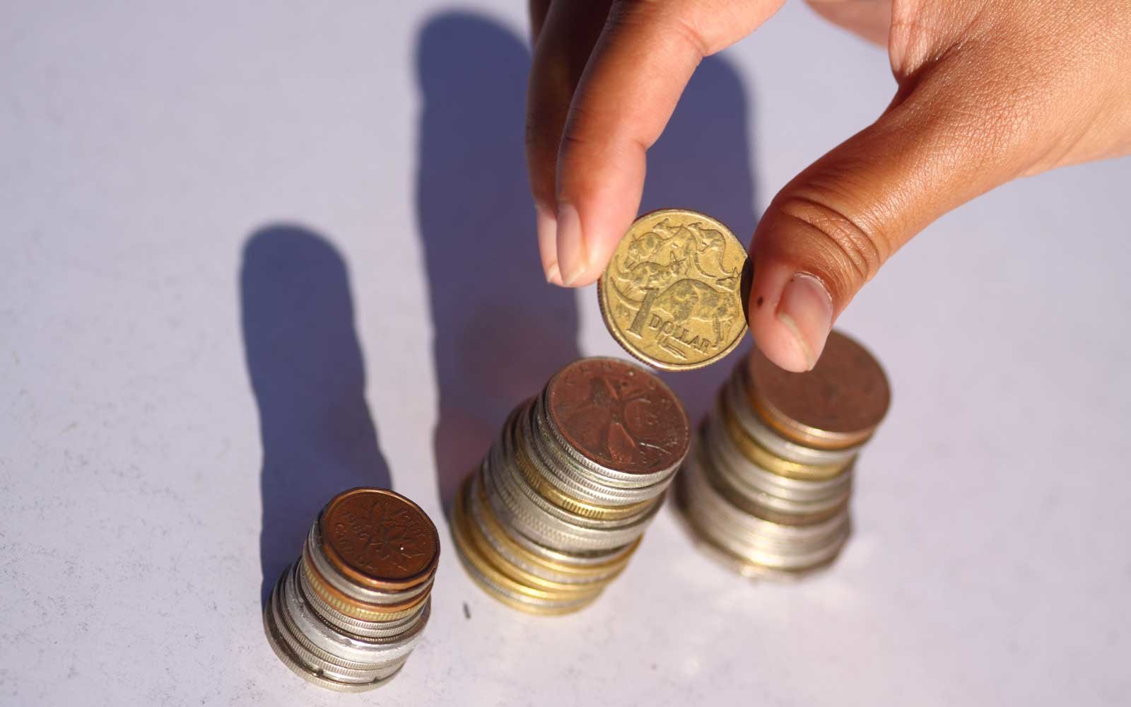 Placing coin on a pile of coins