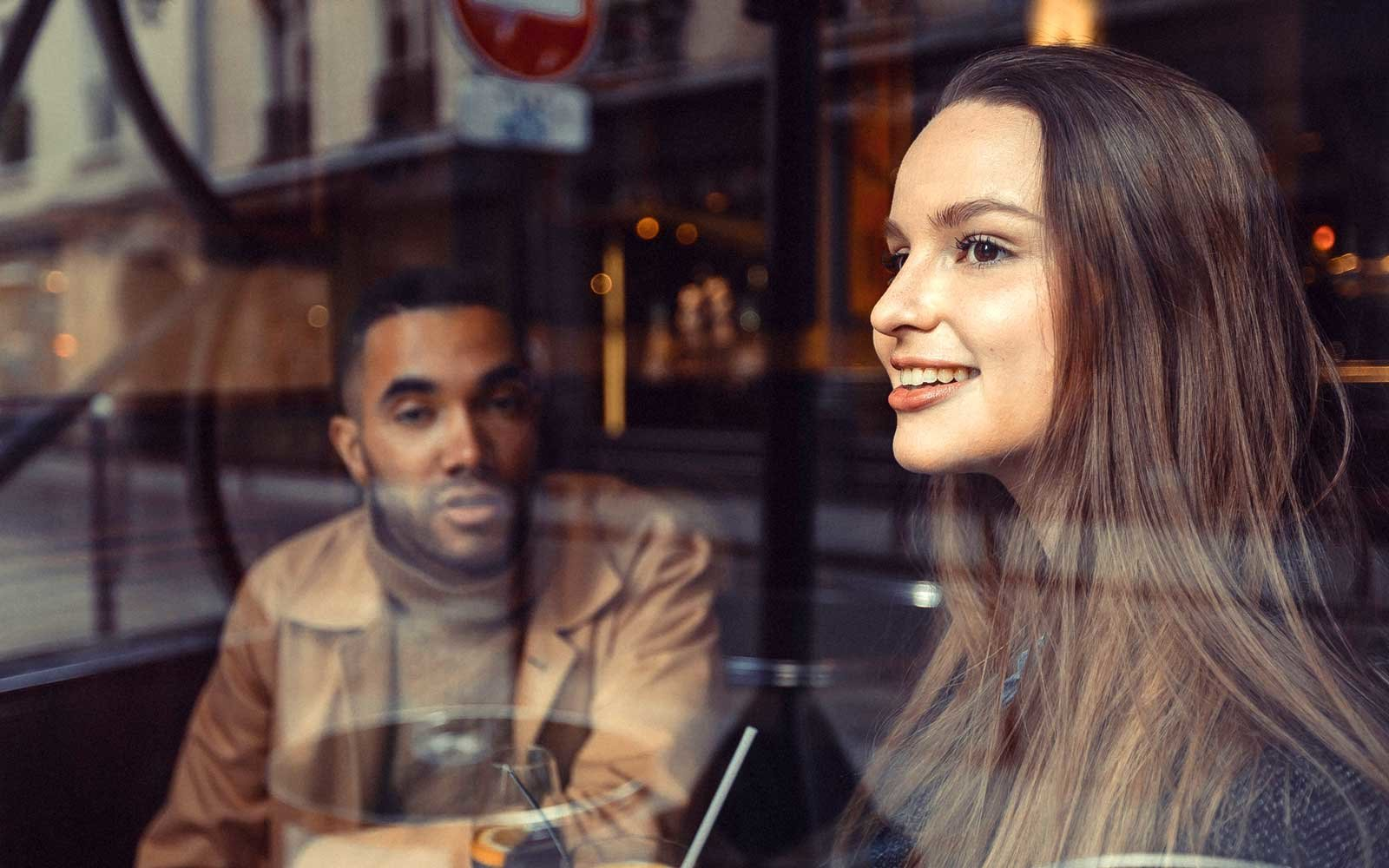 A young couple having conversation at a Cafe in Paris, France.