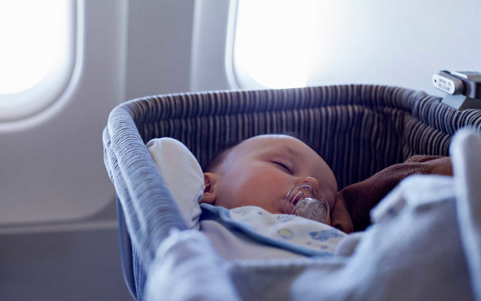 Baby Sleeping In Bassinet On Airplane