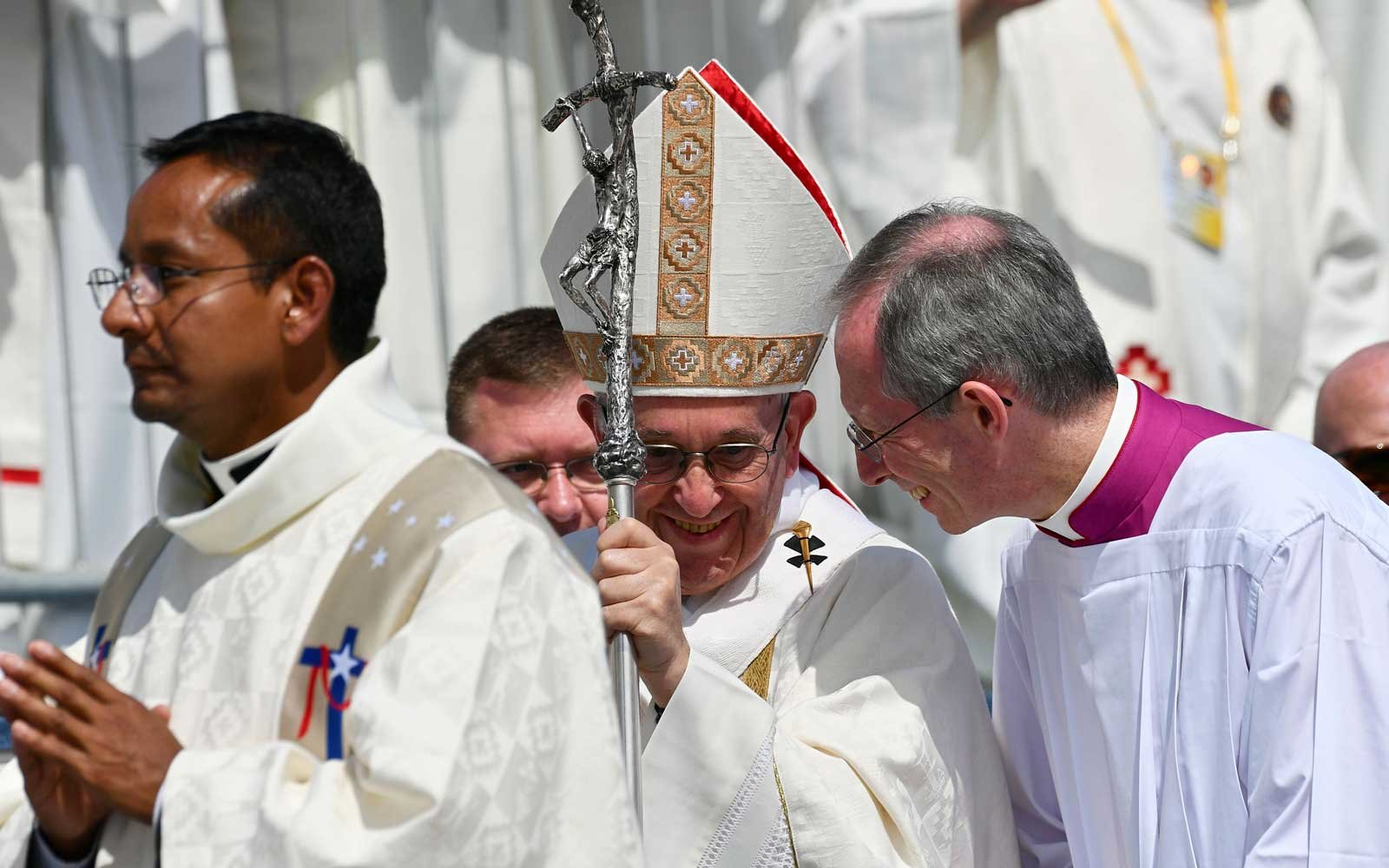 Pope Francis (C) smiles as he walks to the altar set at Lobitos Beach, near the northern Chilean city of Iquique, where he will celebrate an open-air mass on January 18, 2018