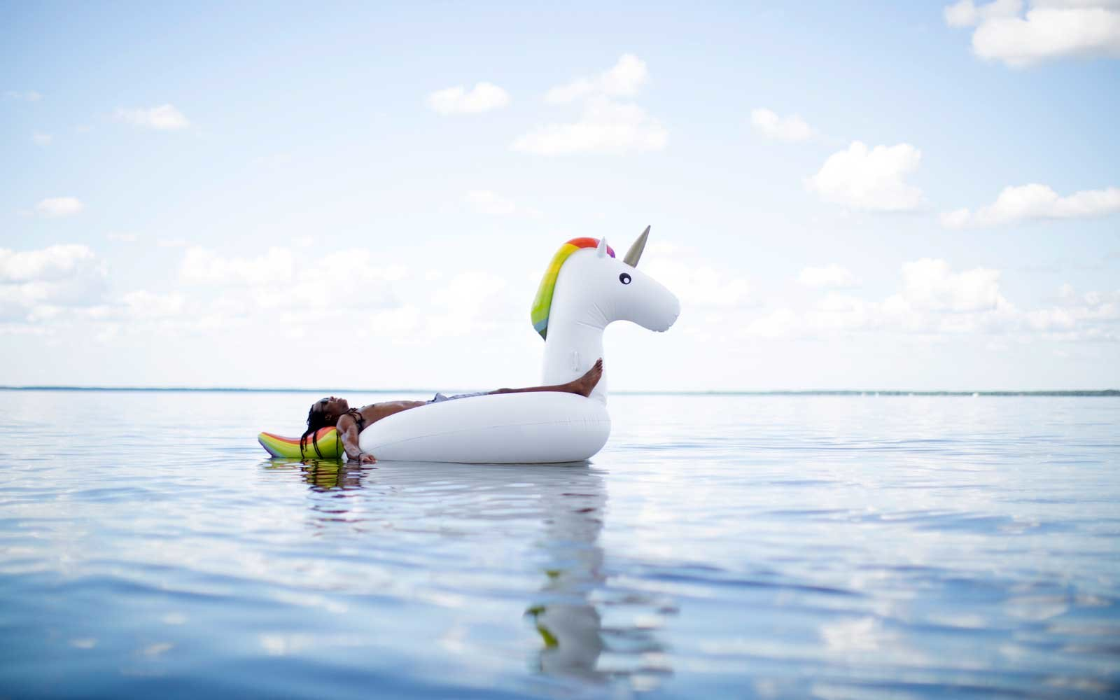 Man lying back on inflatable unicorn in sea, Santa Rosa Beach, Florida