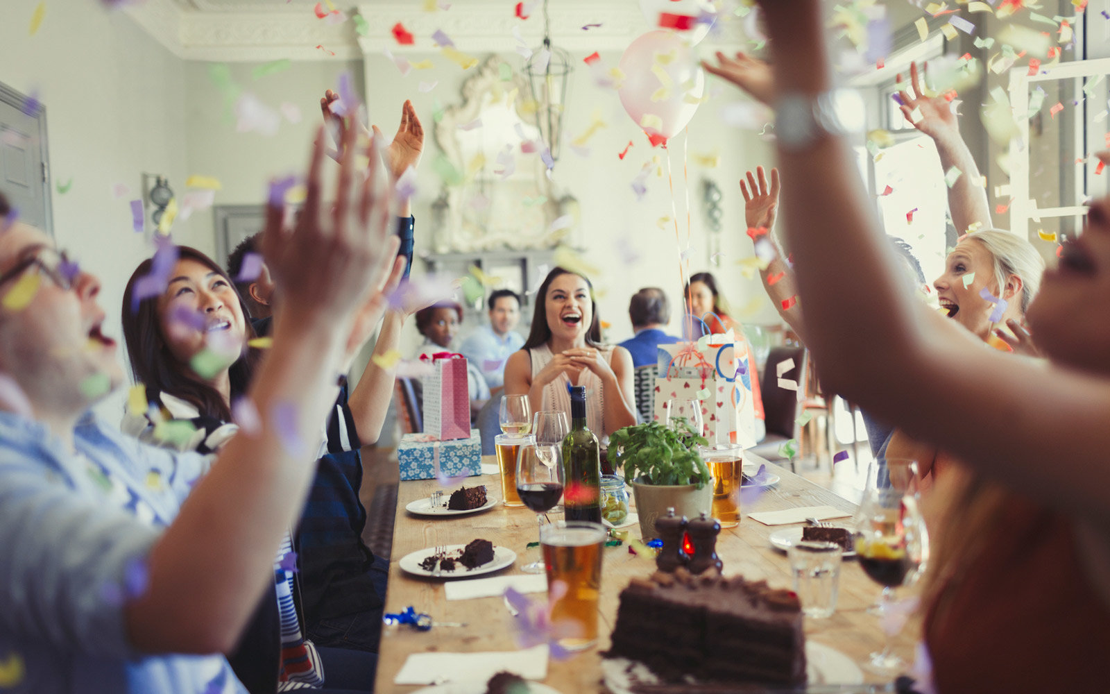 Friends celebrating birthday throwing confetti overhead at restaurant table