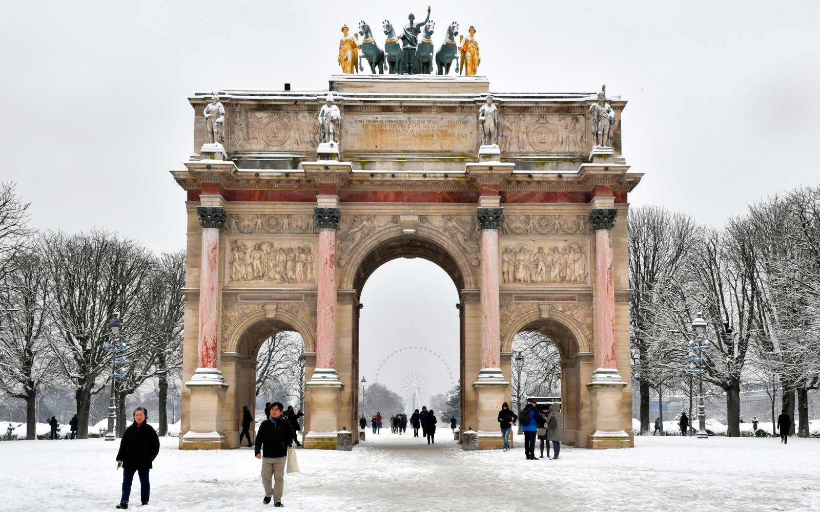 People pass by the Arc de Triomphe du Caroussel as they walk through the snow covered Tuileries garden on February 7, 2018 in Paris.