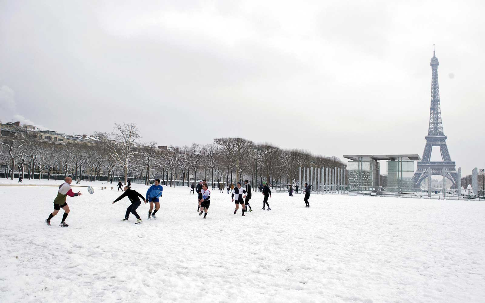 Men play rugby on a snow-covered Champs de Mar