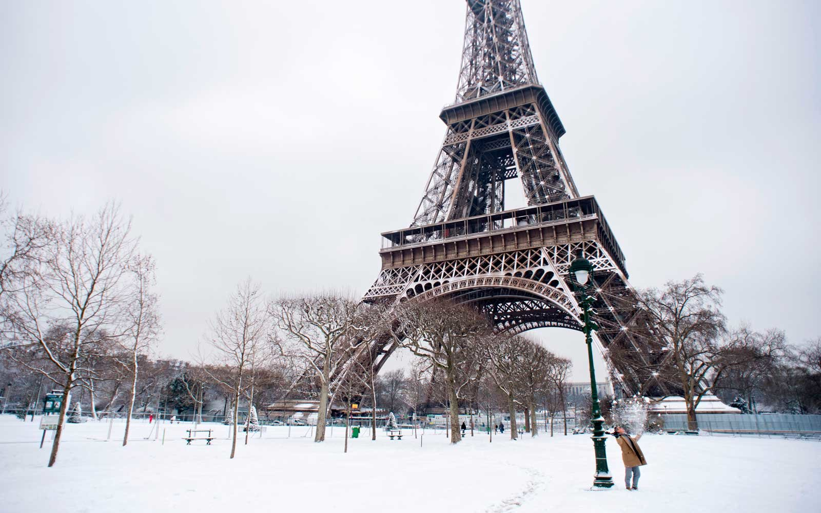 A man plays with snow in the Champ de Mars garden near the Eiffel tower on February 7, 2018 following heavy snowfall in Paris.