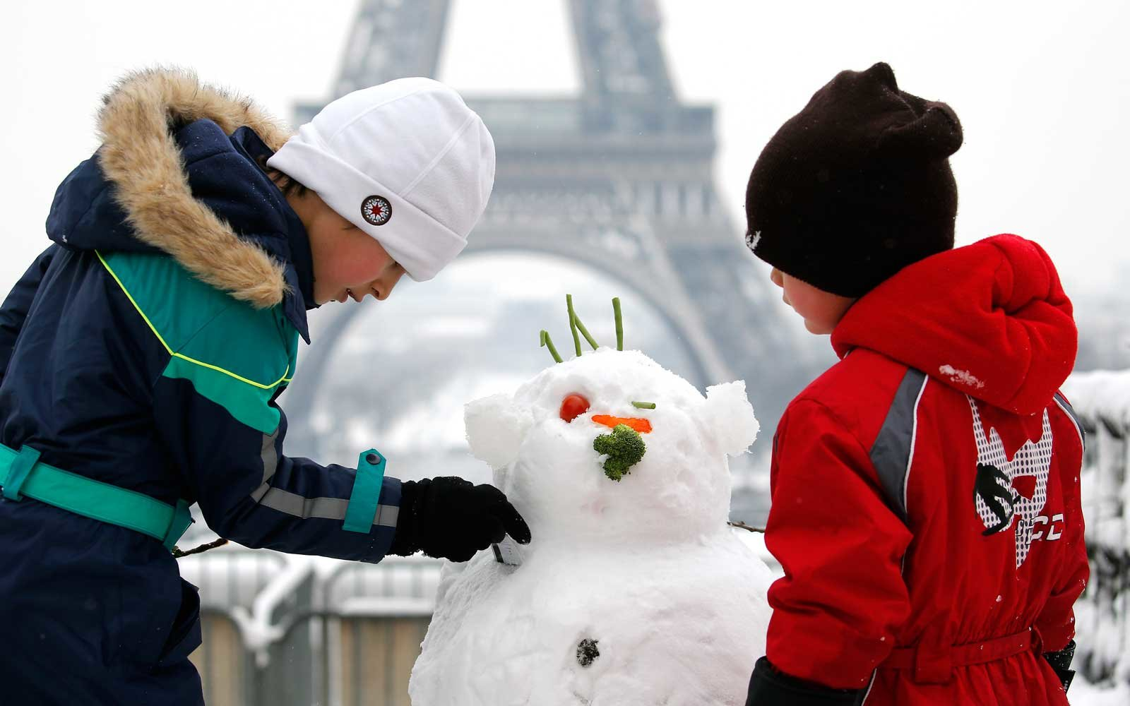 Children make a snowman in front of the Eiffel Tower