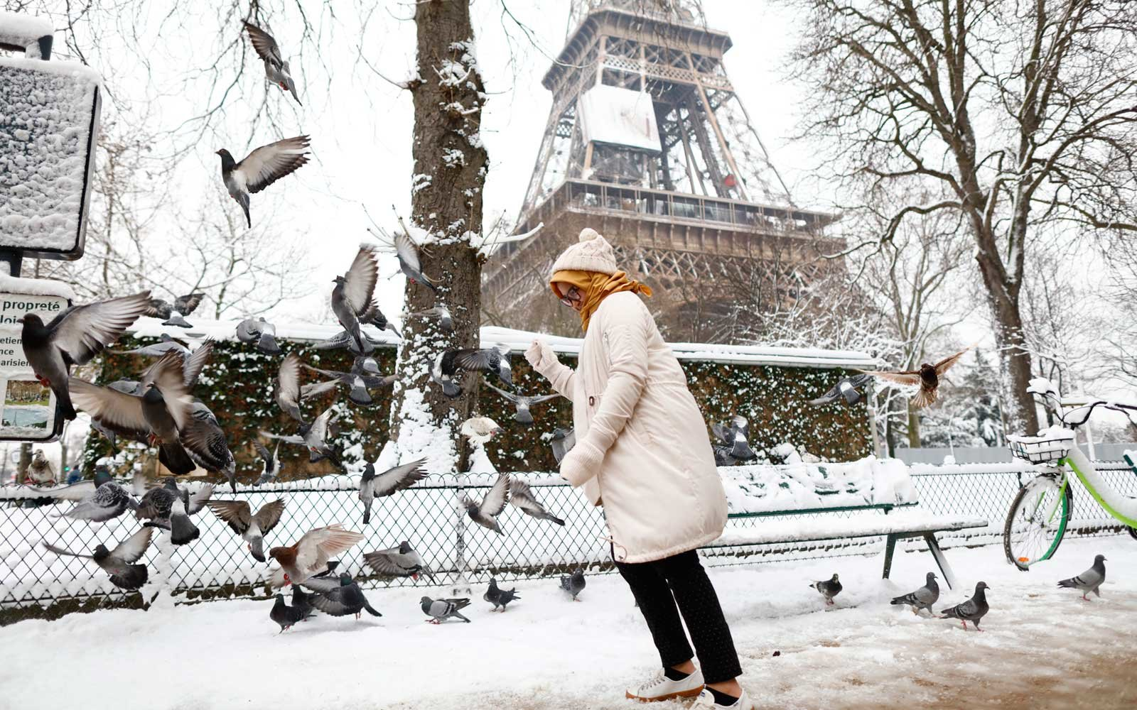 People walk through the snow in Paris, France on February 7, 2018 following heavy snowfall.