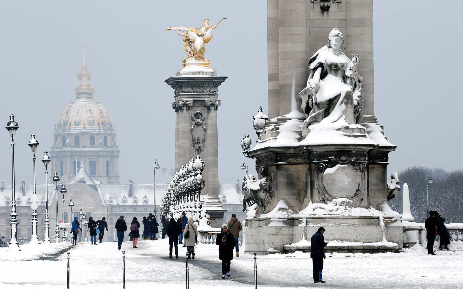 People walk on the snow-covered Pont Alexandre III bridge on February 7, 2018 in Paris, France.
