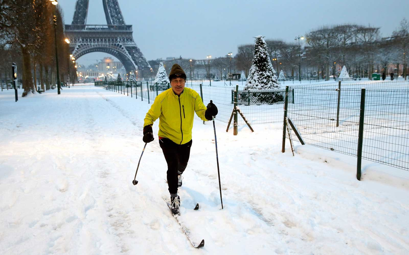 A man enjoys skiing in the Champs de Mars garden covered by snow near the Eiffel Tower on February 7, 2018 in Paris, France.