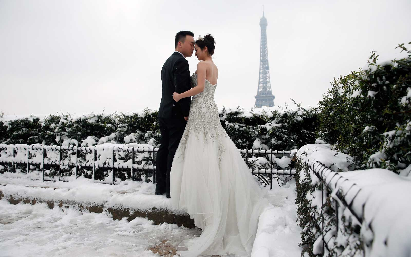 A wedding couple  pose for their own photographer in front of the Eiffel Tower at the snow-covered Trocadero square on February 7, 2018 in Paris, France.