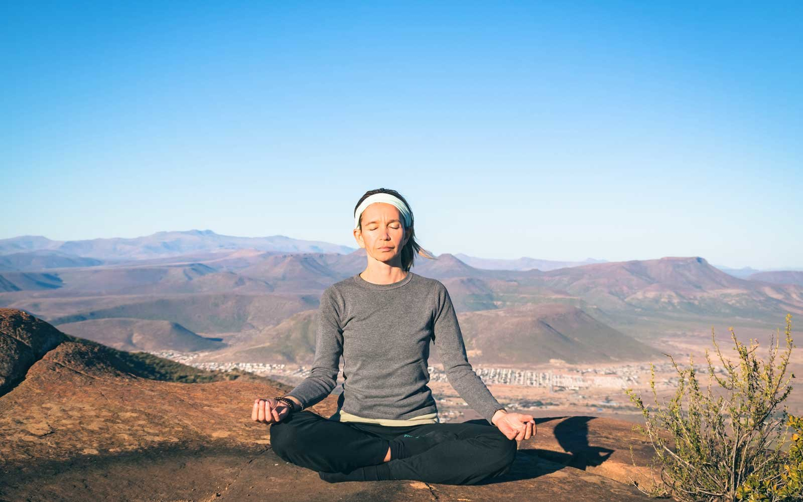Woman Practicing Yoga On Rock At Mountain Peak Against Blue Sky During Sunny Day