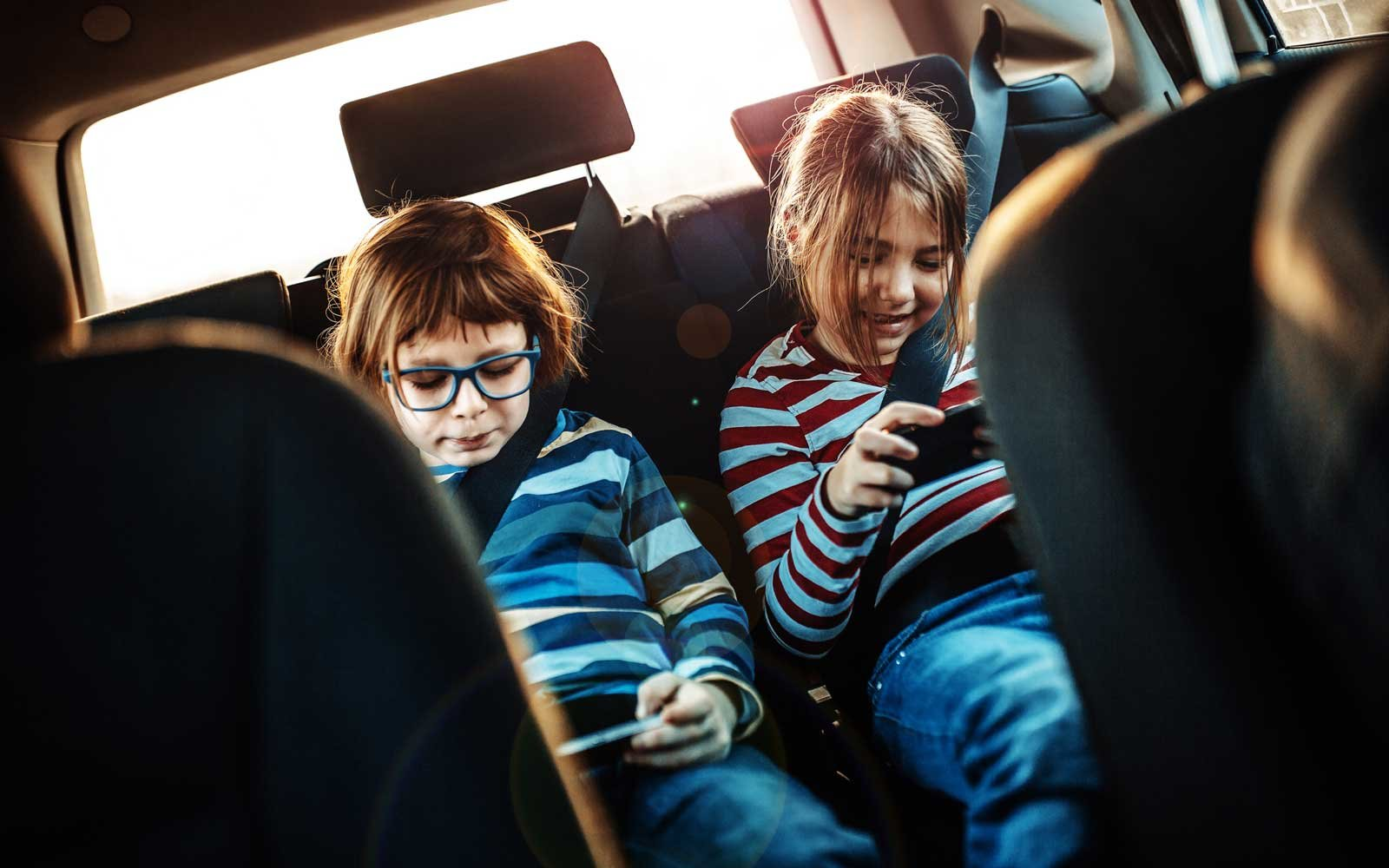 Siblings on smartphones in the backseat