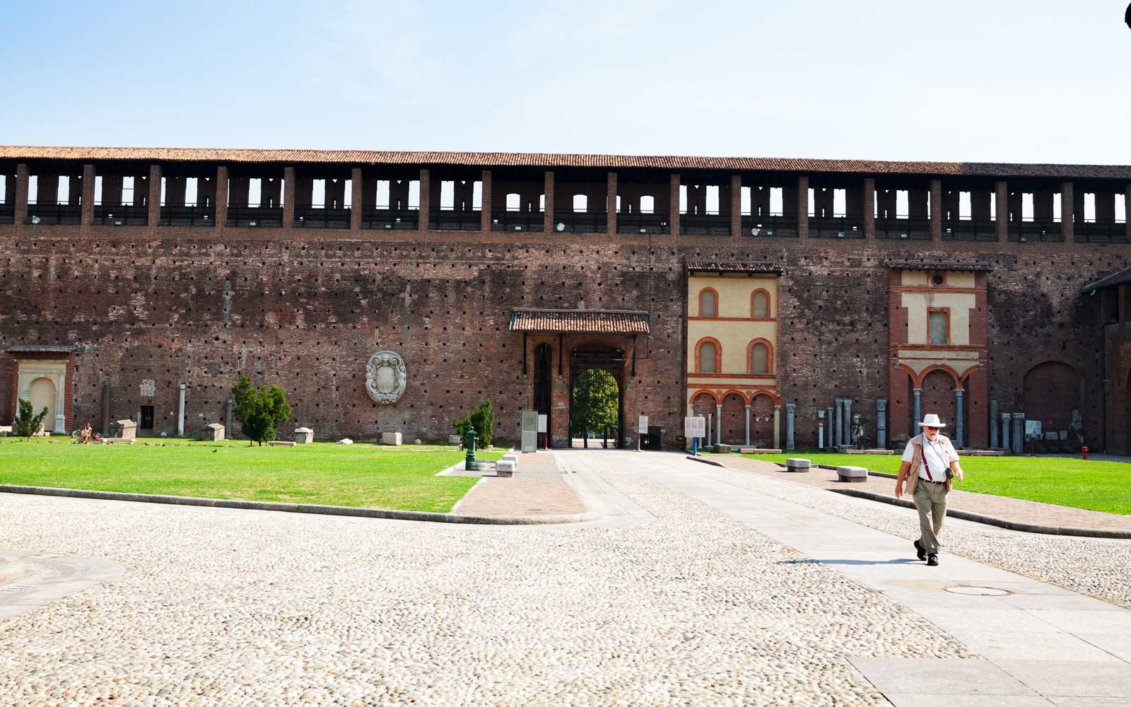 A senior man with beard is passing courtyard of Castello Sforzescoin summer sunshine.